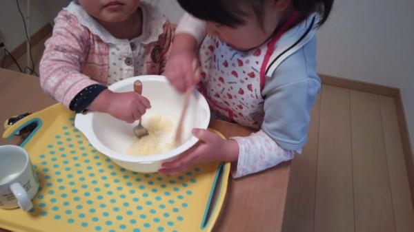 2歳と5歳がボウルの中の砂糖とバターを混ぜている様子
