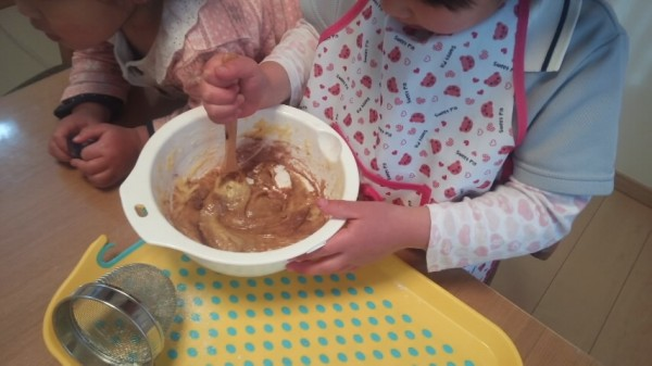 ココアの入ったボウルを混ぜる5歳児