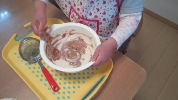 生地の入ったボウルを混ぜる5歳児