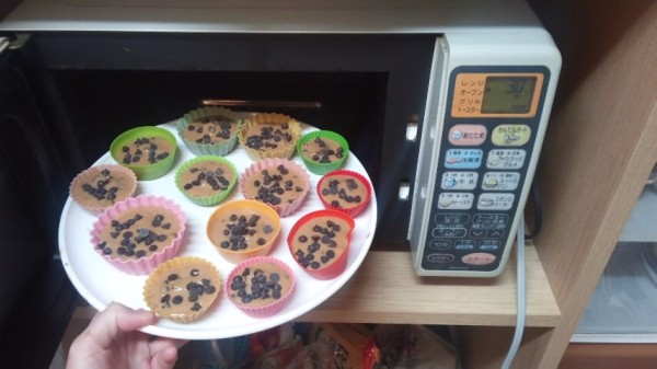 オーブンにチョコチップマフィンの生地を入れているところ