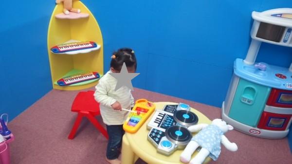 Bのくにのおもちゃのおうちの中で楽器で遊んでいる2歳児