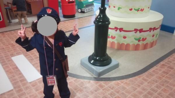 ニューレオマワールド内のごっこタウンで郵便やさんの衣装を着た5歳児